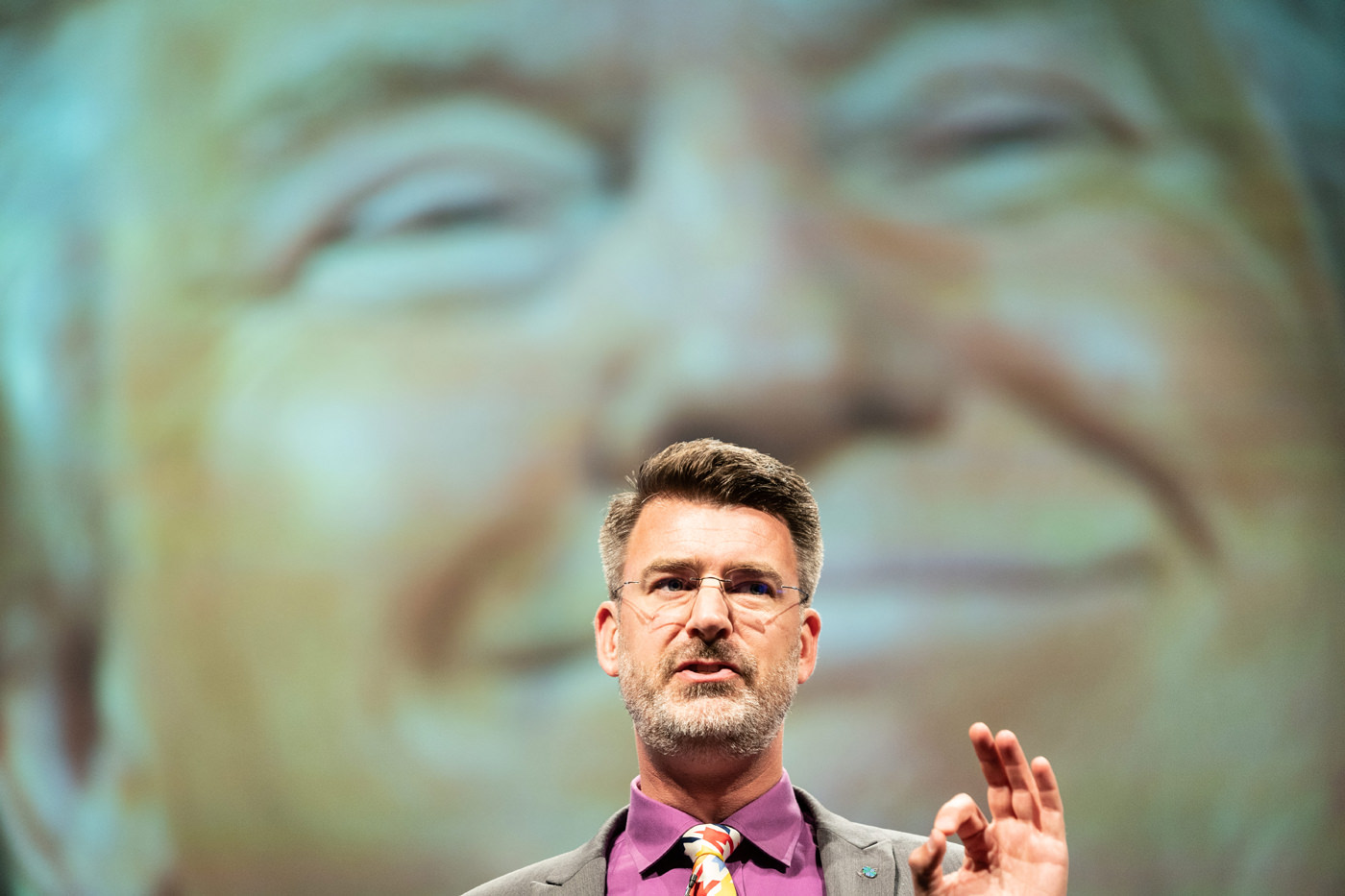 Peter Zeihan presents ​The New World (Dis)Order at CFA Annual Conference 2019 Trump projected behind him