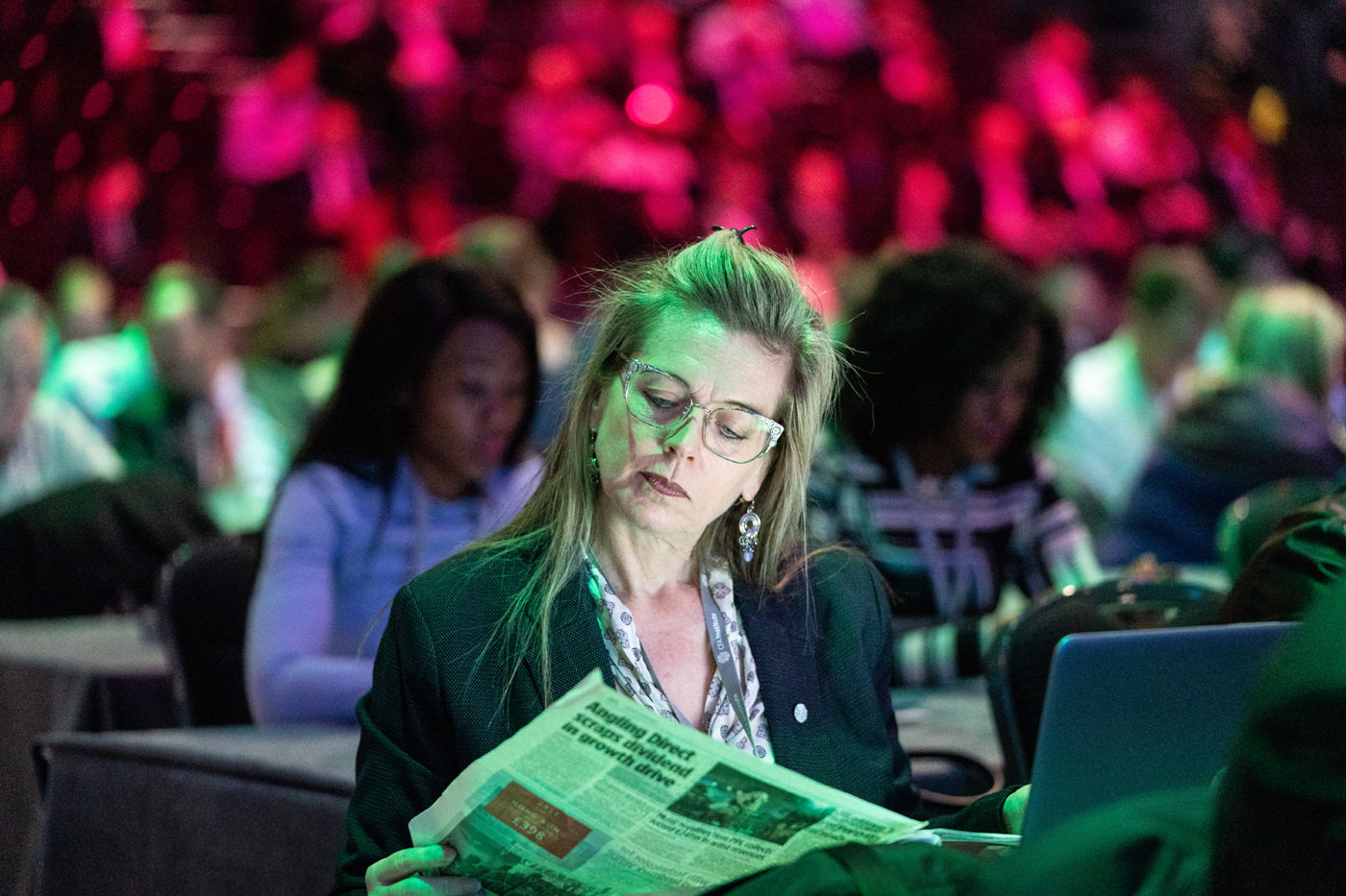 A delegate reads a newspaper at the CFA Annual Conference ExCel London