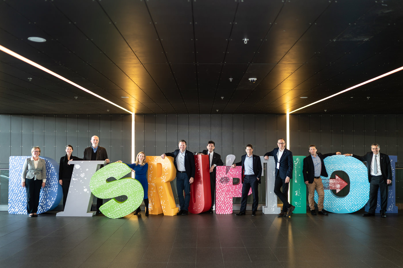 The CFA Society of the UK team at the 2019 Annual Conference surrounded by giant letters spelling Disruption